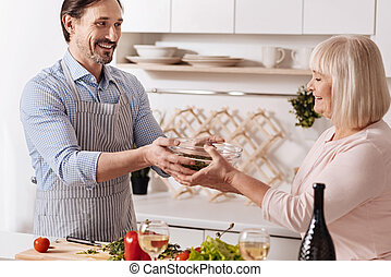 Cheerful man cooking salad with his mother in the kitchen