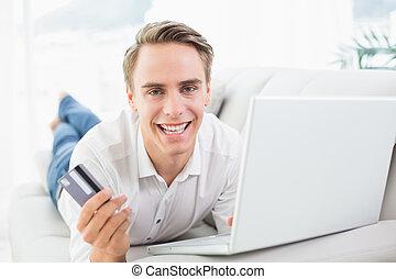 Cheerful man doing online shopping