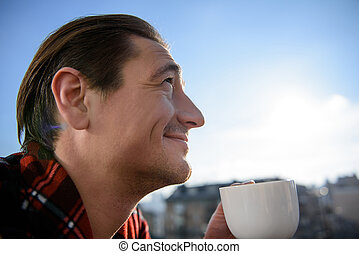 Cheerful man drinking coffee on terrace in the morning