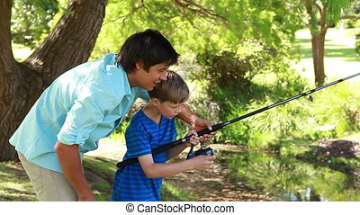 Cheerful man fishing with his son