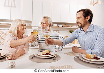Cheerful man greeting his parents with holiday at home