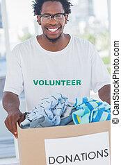 Cheerful man holding donation box