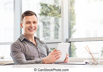 Cheerful man holding tablet