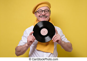 Cheerful man holds the vinyl in hand