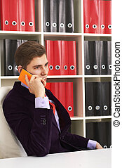 Cheerful man in office talking the phone