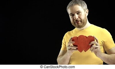 Cheerful man in yellow tshirt holds two red heart shapes. Love, romance, dating, relationship concepts. Black background. 4K shot