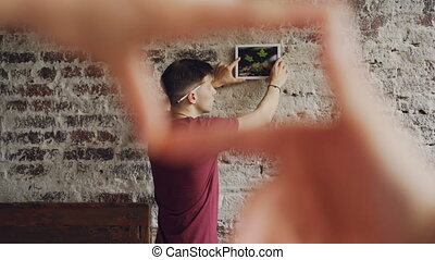 Cheerful man is choosing place for modern picture on brick wall while his wife is making frame shape with her fingers and looking at him, female hands in foreground.