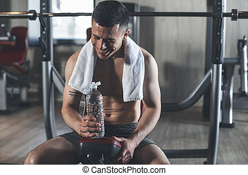 Cheerful man is quenching thirst after workout in gym