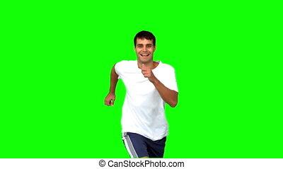 Cheerful man jogging on green screen