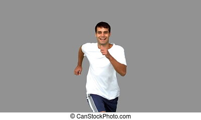 Cheerful man jogging on grey screen in slow motion