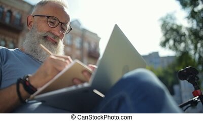 Cheerful man looking at laptop while making notes
