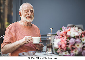 Cheerful man of old age waiting for woman in cafe