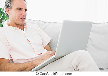 Cheerful man on his couch using laptop