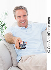 Cheerful man on his couch watching tv