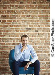Cheerful man on the brick wall