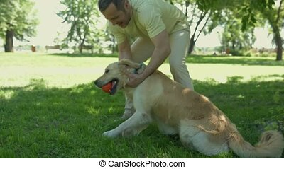 Cheerful man playing with his dog in the park
