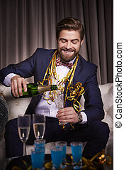 Cheerful man pouring a champagne flute of champagne