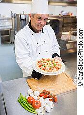 Cheerful man presenting a pizza