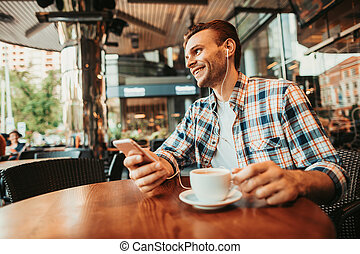 Cheerful man relaxing at desk in cafe