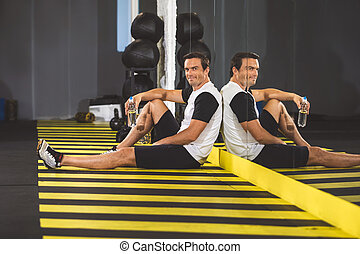 Cheerful man relaxing on floor in gym