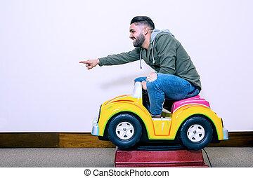 Cheerful man riding on kids car