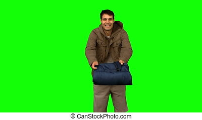 Cheerful man rolling out his sleeping bag on green screen in...