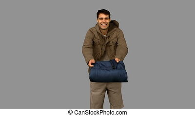 Cheerful man rolling out his sleeping bag on grey screen in...