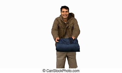 Cheerful man rolling out his sleeping bag on white screen in...