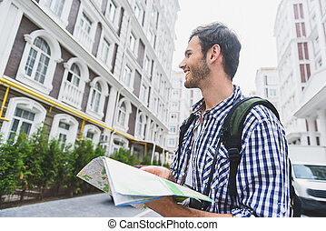 Cheerful man searching correct direction in town