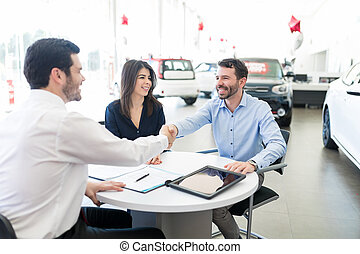 Cheerful Man Shaking Hands With Car Seller