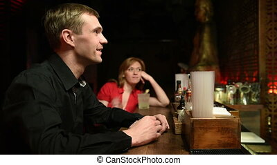 cheerful man sitting at the bar. drinking alcohol from a stack.