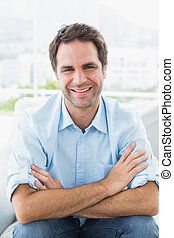 Cheerful man sitting on the couch smiling at camera