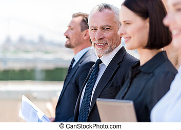 Cheerful man standing with his colleagues