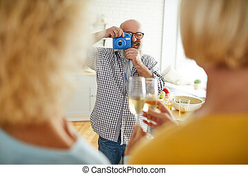 Cheerful man taking photo of friends