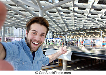 Cheerful man taking selfie and pointing
