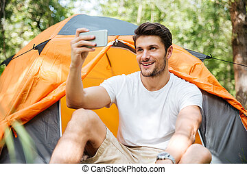 Cheerful man tourist taking selfie with mobile phone in forest