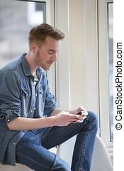 Cheerful Man using his phone at home.