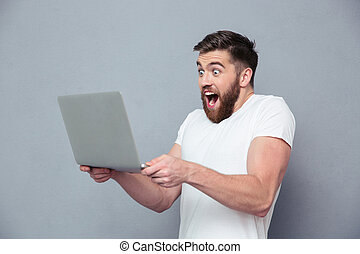 Cheerful man using laptop computer