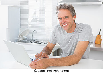 Cheerful man using laptop in kitchen