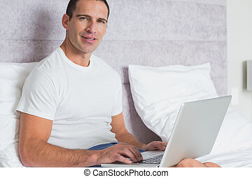 Cheerful man using laptop on bed