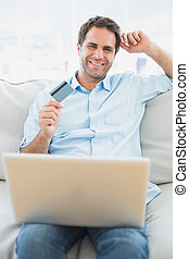 Cheerful man using laptop sitting on sofa shopping online