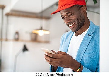 Cheerful man using mobile during labor