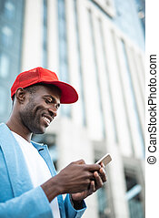 Cheerful man using modern mobile