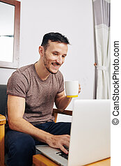 Cheerful man using social media on laptop