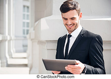 Cheerful man using tablet