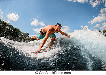 man wakesurfer rides along the wave and touches the spray of water with his hand