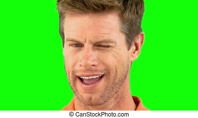 Cheerful man winking an eye on green screen in slow motion