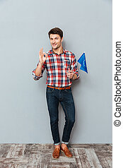 Cheerful man with flag of Europe Union showing ok sign