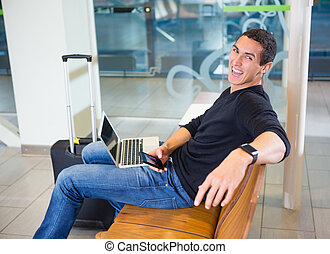 Cheerful Man With Mobile Phone And Laptop In Airport