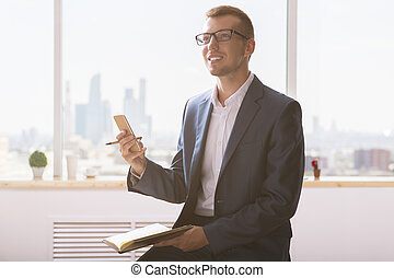 Cheerful man with notepad using cellphone